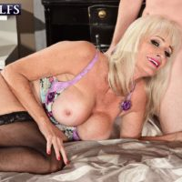 Blonde granny Leah L'Amour gives her guy toy a hand job in lingerie and hose