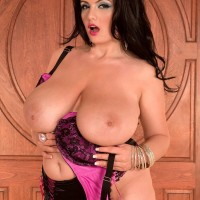 Curvy brunette MILF Arianna Sinn letting large tits loose from bra in hosiery
