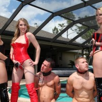 Uber-sexy females in spandex attire and hip high boots manhandle collared male slaves by a pool