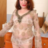 Aged redhead peels off semitransparent clothing and lingerie to pose naked in kitchen