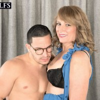 MILF over 50 Catrina Costa seducing stud in glasses wearing short micro-skirt and pumps