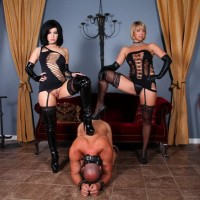 Stellar Mistresses Belle Noir and Brianna manhandle collared male submissive in fetish outfit