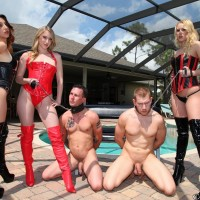 Three Mistresses in fetish apparel manhandle 2 collared male slaves on the pool patio