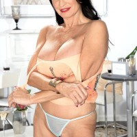 Top older X-rated star Rita Daniels exposes her giant fun bags and shows her panties as well