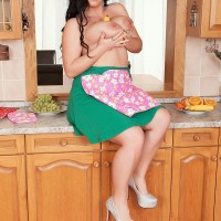 Brown-haired solo female Juliana Simms letting large melons free from sundress in kitchen
