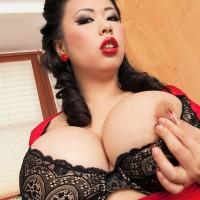 Oriental MILF XXX actress Tigerr Benson unsheathing large fun bags from lingerie in kitchen