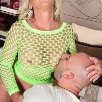 Sandy-haired cougar Brandi Jaimes tempts a dude in a transparent fishnet dress and high-heeled shoes
