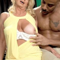 Sandy-haired grannie Nikki Chevious works on seducing a ebony boy in a yellow sundress