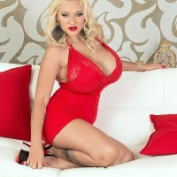 Sandy-haired MILF Dolly Fox letting massive hooters loose from red dress in stilettos