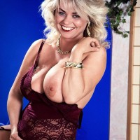 Light-haired MILF Michelle Willings holds her immense natural breasts in garters and hose