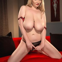 Blond MILF Micky Bells deep throats on her own hard nipples while holding her massive tits