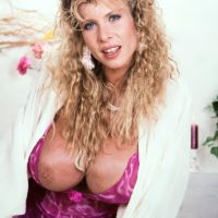 Ash-blonde MILF with superb legs Lynden Johnson sets forward her large knockers in solo act