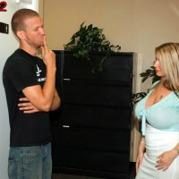 Yellow-haired secretary Summer Sinn demonstrates her massive titties at the office place in a long microskirt