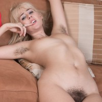 Blond solo chick Aali Rousseau parts her hairy beaver during a close up in bare feet