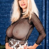 Blonde solo model Alexis Love holds her gigantic titties after unsheathing them from transparent top