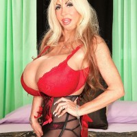 Platinum-blonde solo model Elizabeth Starr displays her monster melons in a crimson bra