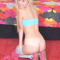 Yellow-haired teenager Naomi Woods strips off her microskirt and pulls down her white hosiery