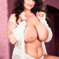 Dark haired girl Lisa Miller sets her immense boobs free on her bed in white panties