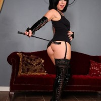Dark haired Dominatrix Belle Noir flaunting ultra-cute and smoothly-shaven coochie in ebony spandex boots