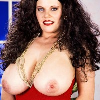 Dark-haired chick Cathy Patrick holds her huge titties after pulling out them from a red dress