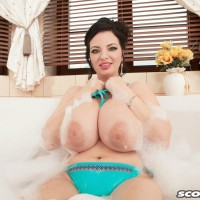 Black-haired MILF Joana Blessing letting gigantic all natural hooters loose from bikini in bath