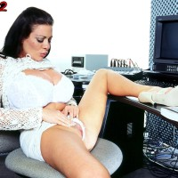 Dark-haired MILF Linsey Dawn McKenzie exposes her monster-sized funbags at her office desk