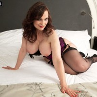 Dark haired MILF over 50 Michaela O'Brilliant showcasing massive hooters before providing BJ