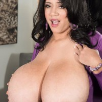 Brunette MILF Roxi Red letting monster-sized breasts free from purple jumper
