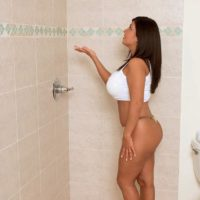 Brown-haired solo female Daylene Rio unsheathing humungous moist Latina boobs in shower