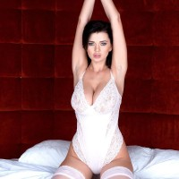 Brunette solo girl Sha Rizel frees her immense melons from body-suit in milky nylons