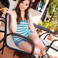 Brown-haired nubile Kasey Warner slurps a banana before whipping out her teenie tits outdoors