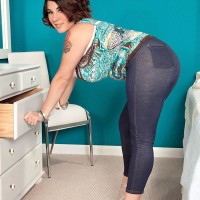 Plumper brown-haired solo female Elaina Gregory unleashing titties in jeans and high heeled shoes