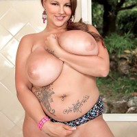 Plumper MILF model Terri Jane letting hefty boobs fall loose from bra outdoors in high heeled shoes