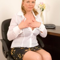 Fully-clothed aged dame exposing monster-sized titties before spreading hairy cunny in office place