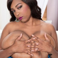 Black solo model Rachel Raxxx exposing gigantic juggs from boulder-holder in black pantyhose