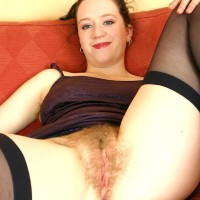 European amateur flashing unshaven pits before spreading fur covered fuckbox on couch