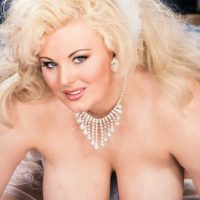 Notorious platinum-blonde pornographic starlet Toni Evans lets her humungous titties fall loose in over the knee hosiery