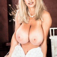 Notorious pornstar Alexis Love uncups her immense boobs in milky hosiery and red high heels