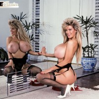 Well-known XXX actress Big-boobed Dusty presses her hefty juggs up against a mirror