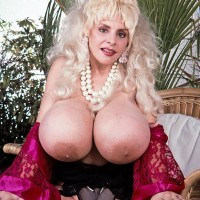 Legendary pornostar Lulu Devine extracts her massive tits in see thru pantyhose and garters