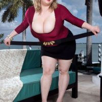 Fat platinum-blonde female Laddie Lynn demonstrates her upskirt bloomers along with her ample cleavage