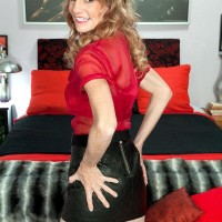 Enticing elder woman Denise Day entices a younger boy in leather skirt and pantyhose