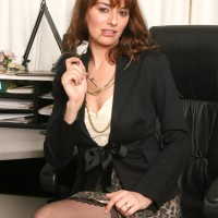 Uber-sexy mature lady strips to her black hosiery only in her home work environment