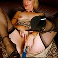Experienced ash-blonde gal hikes up her dress in order to toy her muff in ebony hose