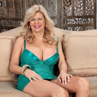 Aged yellow-haired broad Miss Deb looses her gigantic tits from her lingerie on a chesterfield