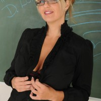Aged golden-haired dame clad glasses strips nude in front of chalkboard in classroom