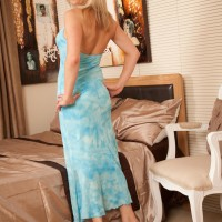 Aged blond model flashing huge juggs and hairless cunny after peeling off dress