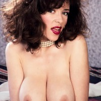 Mature X-rated star Diana Wynn whips out her immense breasts from her retro styled brassiere