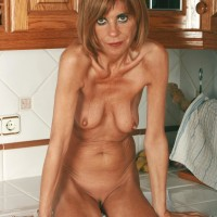 Middle old housewife peels off denim jeans and panties to model nude in kitchen