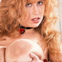 All-natural red-haired Tabatha Towers plays with her massive juggs in a choker and hose
